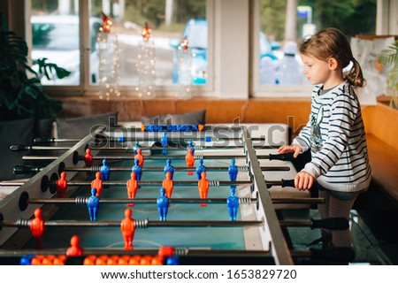 Picture of little beautiful girl with fair hair plays in a table hockey at home