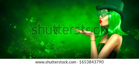St. Patrick's Day leprechaun model girl pointing hand, holding product on green magic background, blowing flying shamrock leaves. Patrick Day pub party, celebrating. Border art design, Widescreen #1653843790
