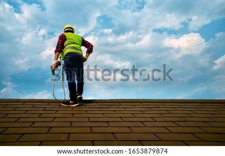 Professional technician Roof repair  Standing action on the roof top Hold the drive screw tool in hand Royalty-Free Stock Photo #1653879874