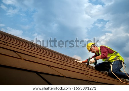 Skilled roof technician worker working Repairing the roof with screws drive tools on the top of the roof #1653891271