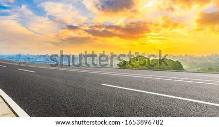Empty asphalt road and city skyline with green mountain at sunrise in Hangzhou,China. #1653896782