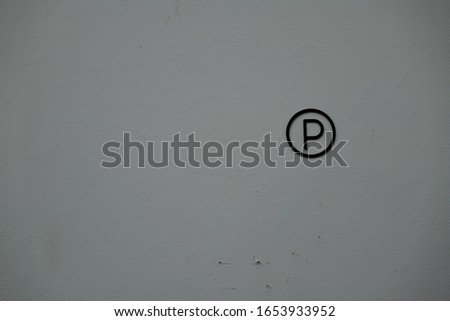 p sign on the white cement wall #1653933952