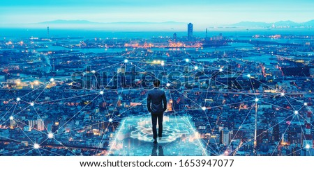 Business technology concept, Professional business man walking on future network city background and futuristic interface graphic at night, Cyberpunk color style #1653947077