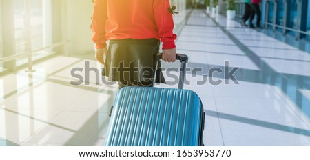 Little girl with travel luggage in the airport #1653953770