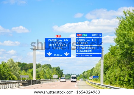 Traffic sign on the highway, toll or autoroute in France with big sqaure blue board ,road  number A31 direction to Paris and another city's names in french language . Transport and sign concept. #1654024963