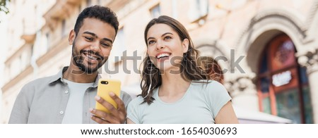 Beautiful happy young couple using smartphone together outdoors panoramic banner, Joyful smiling woman and man looking at mobile phone in city, Love, technology, communication, summer travel concept