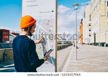 Youthful tourist installing application with city map for tracking gps during touristic sightseeing around urbanity, Caucasian man browsing website on smartphone device standing near location kiosk #1654107964