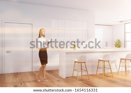 Thoughtful blonde businesswoman with coffee standing in modern pub with white walls, wooden floor, bar counter and white stools. Toned image #1654116331