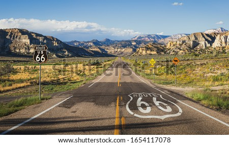 Scenic panoramic view of long straight road on famous Route 66 with historical street signs and paintings in classic american wild western mountain scenery in beautiful golden evening light at sunset Royalty-Free Stock Photo #1654117078