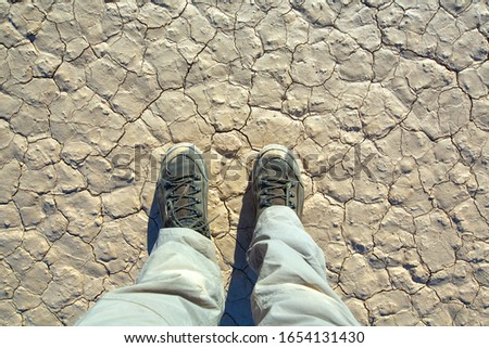 "Man feet with shoes on The Racetrack Playa, or The Racetrack, is a scenic dry lake feature with ""sailing stones"" that inscribe linear ""racetrack"" imprints. #1654131430"
