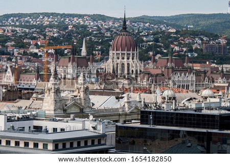 The Hungarian Parliament Building, rooftop view from the tower of St. Stephen's Basilica. In the old town of Budapest, Hungary. Buildings, towers and colorful rooftops. European capital city skyline. #1654182850