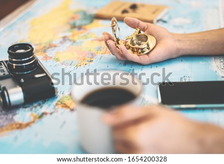 Side view female hands planning vacation with world map and vintage nautical compass - Travel adventure lifestyle people and discovering destinations concept #1654200328