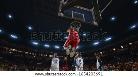 Basketball players on big professional arena during the game. Tense moment of the game. View from below the basket