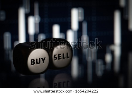 Sell and buy dice on blurred candlestick chart . Close-up stock photo #1654204222
