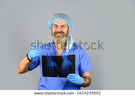 Hospital emergency. Doctor compares results. X ray radiation. Doctor holds pictures of bones. Fracture and bone damage. Doctor examines radiographic snapshot of wrist. Surgeon estimate damages.