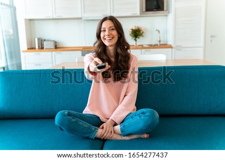Image of a positive smiling optimistic young woman sit indoors at home watch tv holding remote control on sofa. Royalty-Free Stock Photo #1654277437