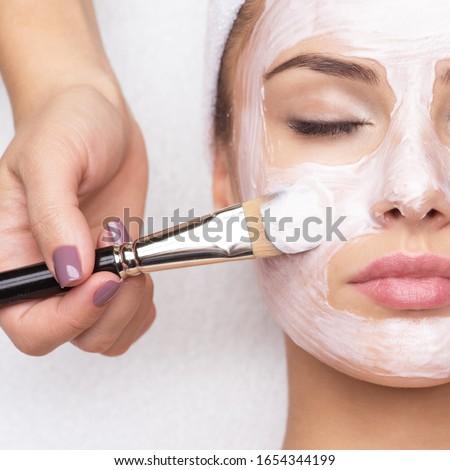 Beautiful young woman receiving facial mask at beauty salon Royalty-Free Stock Photo #1654344199