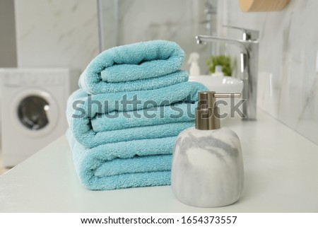 Stack of clean towels and soap dispenser on countertop in bathroom #1654373557
