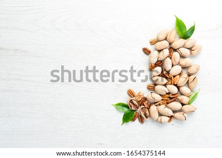 Delicious Pecan nuts on white background Wooden. Top view. Free space for your text. #1654375144