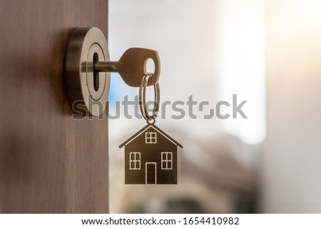 Open door to a new home with key and home shaped keychain. Mortgage, investment, real estate, property and new home concept #1654410982