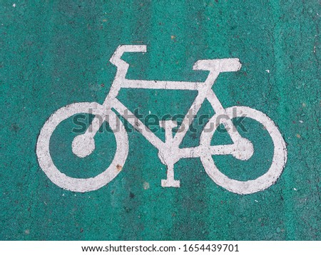 A picture of white bike sign and symbol appearing on the path of bike lane