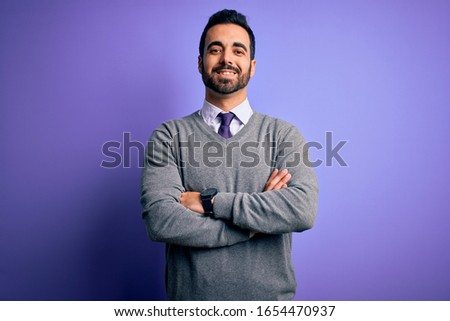 Handsome businessman with beard wearing casual tie standing over purple background happy face smiling with crossed arms looking at the camera. Positive person.