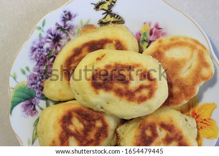 Fresh, small home-baked pancakes with baked goods lie on a plate with a picture of flowers.