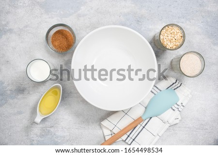Empty bowl and ingredients for baking healthy oat cookies, muffins or cake. Top view flat lay. Kitchen utensils and cooking ingredients on concrete background #1654498534