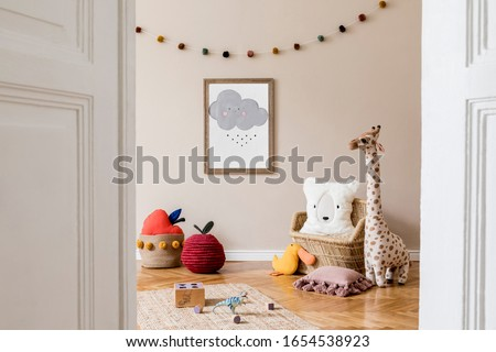 Stylish and beige scandinavian decor of kid room with mock up poster frame, design furnitures, natural toys, hanging colorful cotton balls, teddy bears, plush animal and child accessories. Template