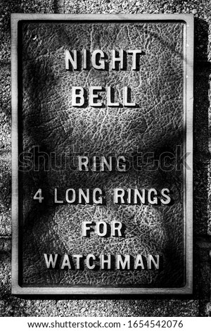 """An old metal sign says """"Night Bell  Ring 4 Long Rings for Watchman"""" posted on a long abandoned industrial building  #1654542076"""