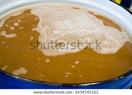 Unboiled wort after removing malts from liquid, homebrewing craft beer #1654545562