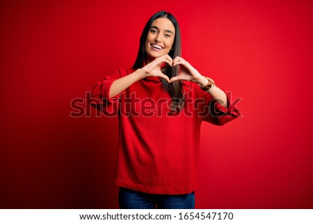 Young beautiful brunette woman wearing casual sweater over isolated red background smiling in love doing heart symbol shape with hands. Romantic concept. #1654547170