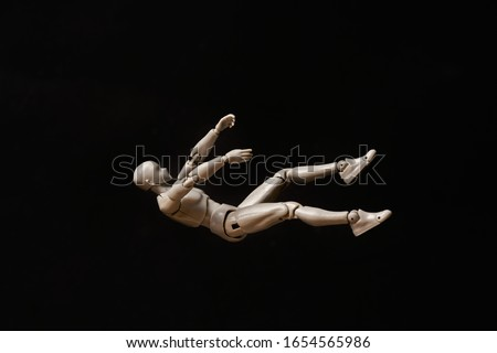 Business and design concept - falling mannequin isolated on black background. falling man Royalty-Free Stock Photo #1654565986