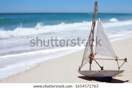 Sail boat toy on sandy beach #1654572763