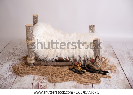 white wooden log bed for newborns Royalty-Free Stock Photo #1654590871