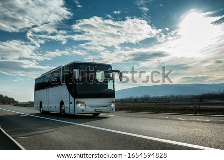 White Modern comfortable tourist bus driving through highway at bright sunny sunset. Travel and coach tourism concept. Trip and journey by vehicle #1654594828