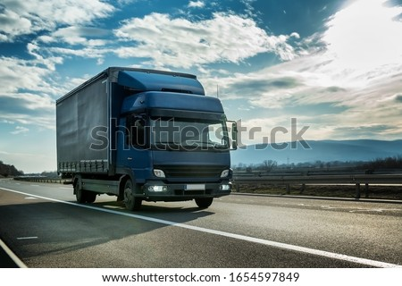 Blue semi trailer truck on a highway driving at bright sunny sunset. Transportation vehicle #1654597849
