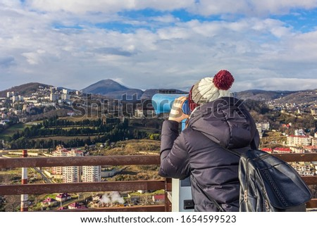 Young woman looking through sightseeing touristic telescope  at the mountains. View from the observation deck (viewing platform). Tourist walk, excursion. #1654599523