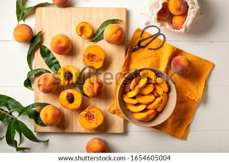Peaches whole fruits with leaves, peaches in halves, peach slices on a white kitchen table. The process of making peach jam, cooking peach dessert on a cutting board. Pastry chef work place. Flat lay #1654605004