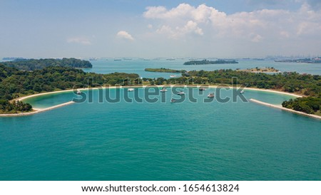 Aerial picture of Lazarus Island in Singapore. View from sea to beach. Sunny warm day. Turquoise water and green forest. Boats anchored in shore water.