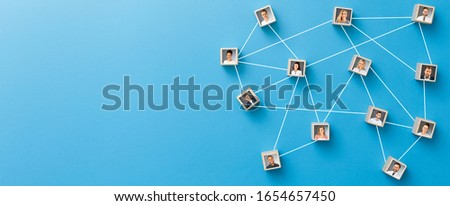 Wooden blocks connected together on blue background. Teamwork, network and community concept. Royalty-Free Stock Photo #1654657450