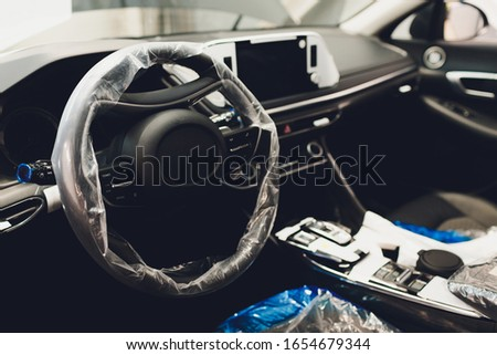 Steering wheel with protective cover on. car pre-sale Royalty-Free Stock Photo #1654679344
