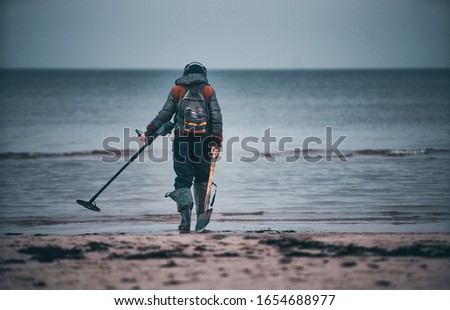 Man with a metal detector on a sea sandy beach. Royalty-Free Stock Photo #1654688977
