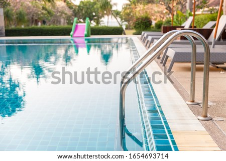 Ladder stainless handrails for descent into swimming pool. Swimming pool with handrail . Ladder of a swimming pool. Horizontal shot. #1654693714
