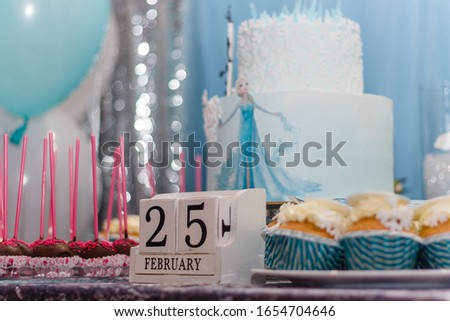 Izmail, Ukraine - February 2019. Winter birthday candy bar, muffins with Frozen cartoon characters. Cubic calender with 25th February date.