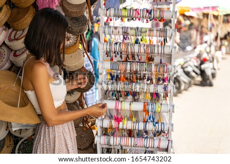 Young beautiful female tourist is choosing souvenirs in street shop and looking at colour bracelets. Local souvenir concept #1654743202