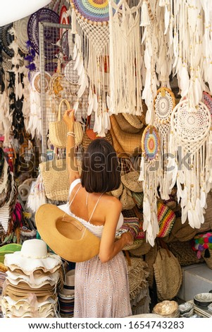 Young woman is strolling among souvenir shops abroad and choosing unique handmade gift. Buying local souvenirs concept #1654743283