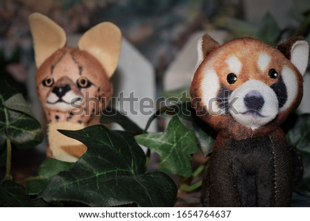 Funny picture with a plush raccoon and cheetah posing in the jungle