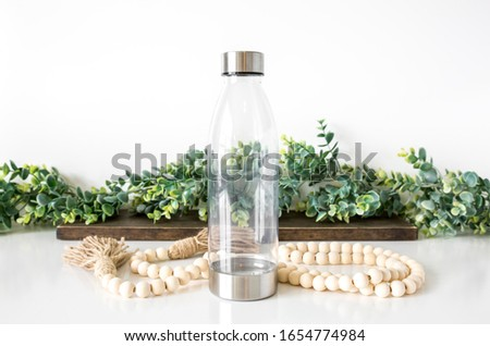 Blank clear and silver water bottle on white background with natural props, beverage bottle mockup