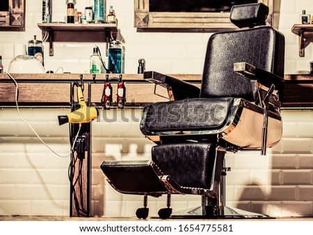 Professional hairstylist in barbershop interior. Barbershop interior. Barber shop chair. Barbershop armchair, modern hairdresser and hair salon, barber shop for men. Stylish vintage barber chair. #1654775581